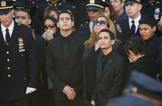 Officer Rafael Ramos' wife Maritza is flanked by sons Justin and Jaden Ramos as they leave Christ Tabernacle Church in Queens after the funeral on Saturday Dec. 27, 2014.Photo by  Tiocfaidh ár lá 1916