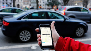 An UBER application is shown as cars drive by in Washington, DC. (Andrew Caballero-Reynolds/AFP/Getty Images)