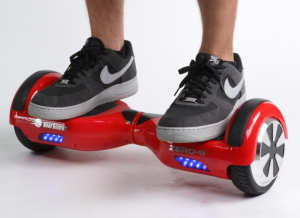 A red self-balancing two-wheeled board with a person standing on it.