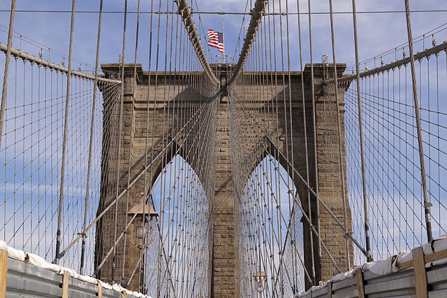 Manhattan-side tower of the Brooklyn Bridge in New York City (USA) with the national flag flying half-staff on top. Photo courtesy of NormanB.